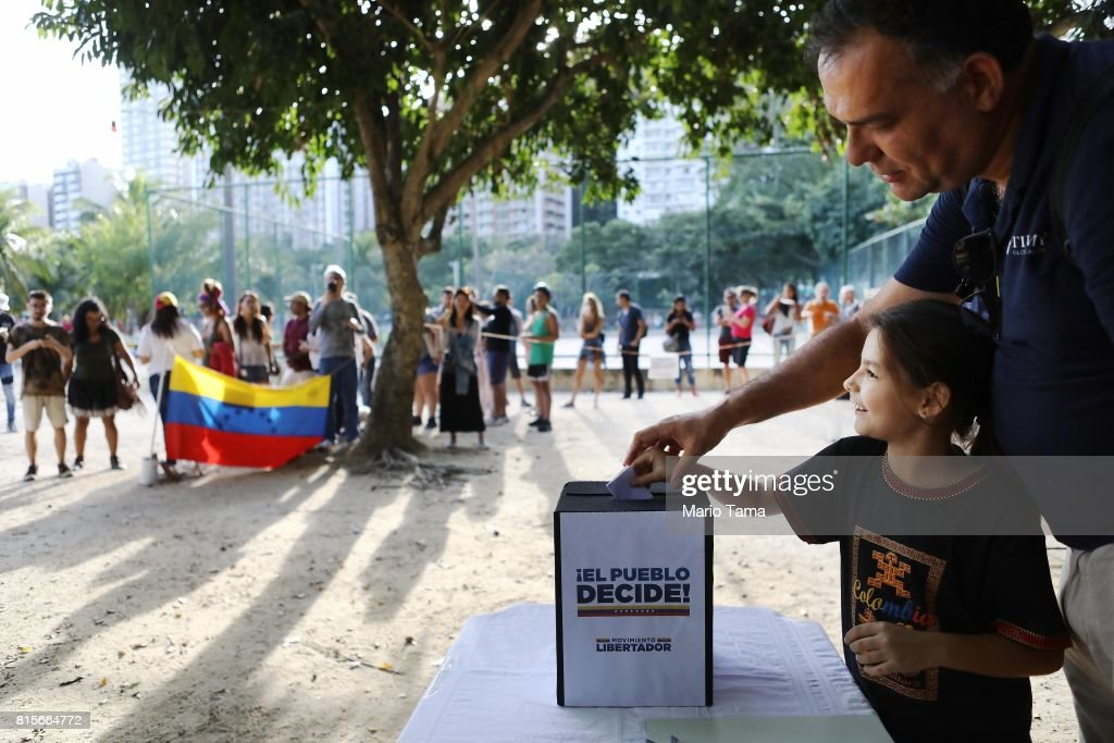 Venezuelan expatriate Hernan Troconis casts his ballot with his daughter as others wait on line during an unofficial referendum, or plebiscite, held by Venezuela's opposition against Venezuela's President Nicolas Maduro's government on July 16, 2017 in Rio de Janeiro, Brazil. Voting was conducted across 2,000 polling centers in Venezuela and in more than 80 countries around the world amidst a severe crisis in Venezuela.