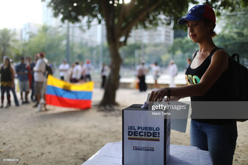 Venezuelan expatriate Iralys Escalona casts her ballot as others wait on line during an unofficial referendum, or plebiscite, held by Venezuela's opposition against Venezuela's President Nicolas Maduro's government on July 16, 2017 in Rio de Janeiro, Brazil. Voting was conducted across 2,000 polling centers in Venezuela and in more than 80 countries around the world amidst a severe crisis in Venezuela.