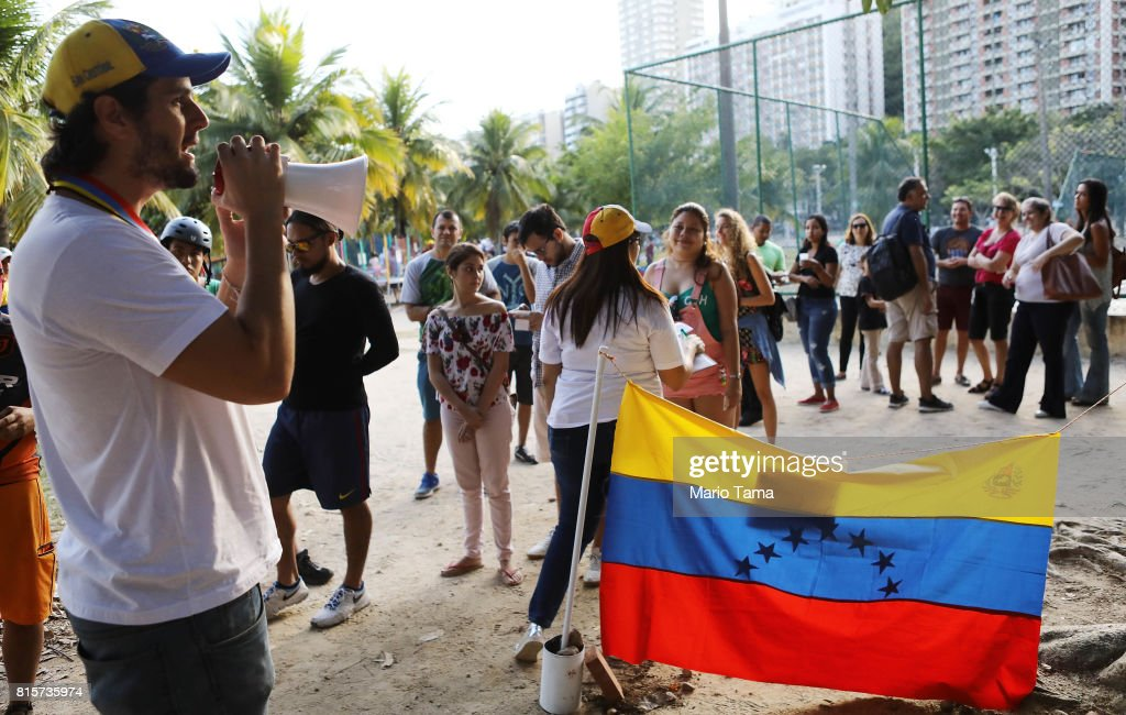 Venezuelan expatriate William Clavijo speaks to other expatriates waiting on line during an unofficial referendum, or plebiscite, held by Venezuela's opposition against Venezuela's President Nicolas Maduro's government on July 16, 2017 in Rio de Janeiro, Brazil. Voting was conducted across 2,000 polling centers in Venezuela and in more than 80 countries around the world amidst a severe crisis in Venezuela.