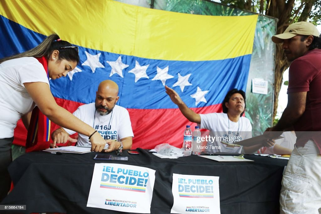 Venezuelan expatriates (FAR L and FAR R) prepare to cast ballots during an unofficial referendum, or plebiscite, held by Venezuela's opposition against Venezuela's President Nicolas Maduro's government on July 16, 2017 in Rio de Janeiro, Brazil. Voting was conducted across 2,000 polling centers in Venezuela and in more than 80 countries around the world amidst a severe crisis in Venezuela.