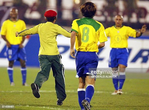 Venezuelan fan runs to hug Brazilian Roberto Carlos 09 October 2004 during the FIFA World Cup Germany 2006 qualifying match between Venezuela and...