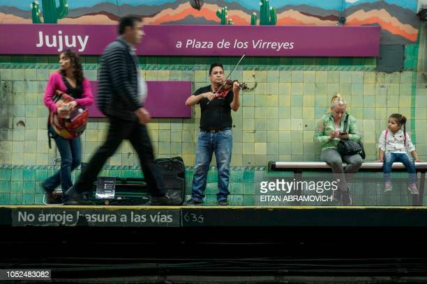 Venezuelan Fedosky Suarez member of the Latin Vox Machine orchestra plays the violin at a subway station in Buenos Aires on October 10 2018 Latin Vox...