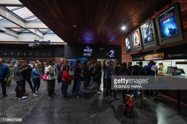 """Venezuelan filmgoers queue to withdraw tickets to watch the first screening in Venezuela of Marvel Studios' """"Avengers: Endgame"""" at a cinema in..."""