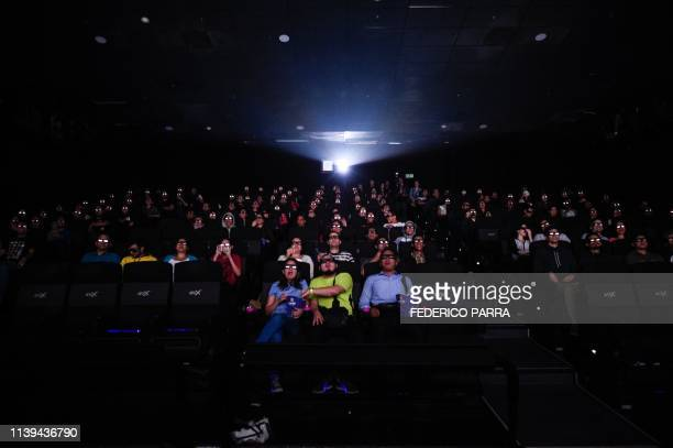 Venezuelan filmgoers watch the first screening in Venezuela of Marvel Studios' Avengers Endgame at a cinema in Caracas on early April 26 2019 The...