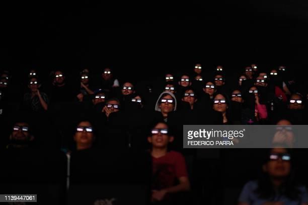 Venezuelan filmgoers watch the first screening in Venezuela of Marvel Studios' Avengers Endgame at a cinema in Caracas on early April 26 2019 The...