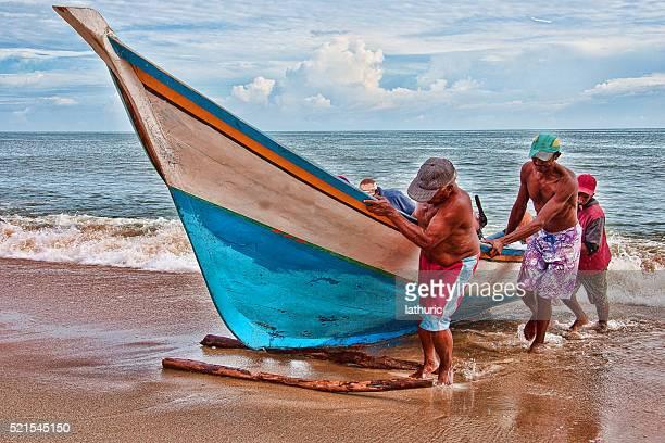 Venezuelan fishermen working together to drag a fishing boat to shore