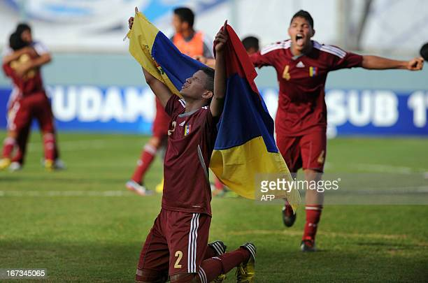 Venezuelan footballer Juan Tineo celebrates with the national flag next to teammate Jose Marrufo at the end of their match against Uruguay during the...