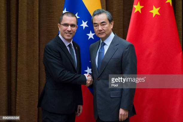 Venezuelan Foreign Minister Jorge Arreaza shake hands with China's Foreign Minister Wang Yi at the Ministry of Foreign Affairs in Beijing on December...
