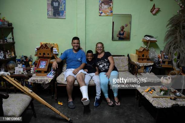 Venezuelan Frankeiber Hernandez and his brother Fraiber Hernandez whose parents emigrated pose with their grandmother Estelita Batista who takes care...