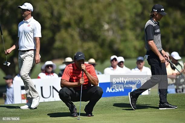 Venezuelan golfer Jhonattan Vegas lines up a putt as Australian golfers Adam Scott and Aaron Baddeley walk past on the second hole on day two of the...