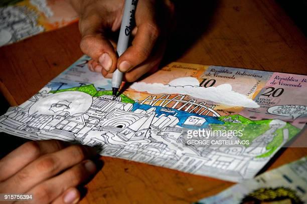 Venezuelan illustrator Jose Leon draws on devalued Bolivar bills, at his workshop in San Cristobal, Venezuela on February 2, 2018. Using devalued...