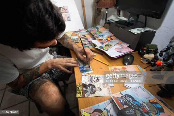 Venezuelan illustrator Jose Leon paints on devalued Bolivar bills, at his workshop in San Cristobal, Venezuela on February 2, 2018. Using devalued...