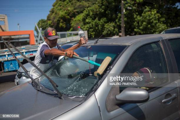 A Venezuelan immigrant who arrived two months ago searching for a job to send money for the rest o the family who stayed in Venezuela washes window...