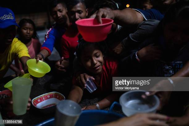 Venezuelan indigenous people of the Warao ethnic group crowd for food distribution before a movie session April 6, 2019 in Pacaraima, Brazil....