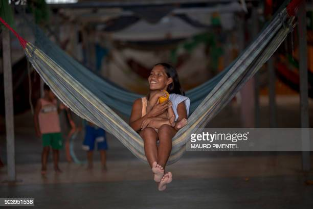 Venezuelan indigenous refugee gives water to her daughter at the Pintolandia shelter in the city of Boa Vista Roraima Brazil on February 24 2018...