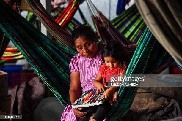 Venezuelan indigenous woman and a girl of the Warao tribe rest in a hammock at the Janokoida shelter where they have been taking refuge in Pacaraima...