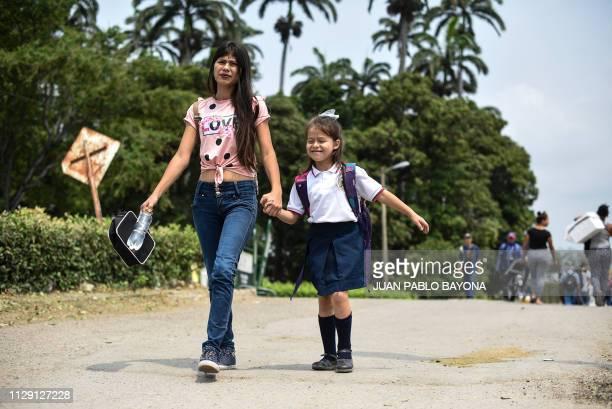 TOPSHOT Venezuelan Leidy Navarro walks with her daughter Valentina Caceres back to their home in Urena Venezuela after picking her up at school in...