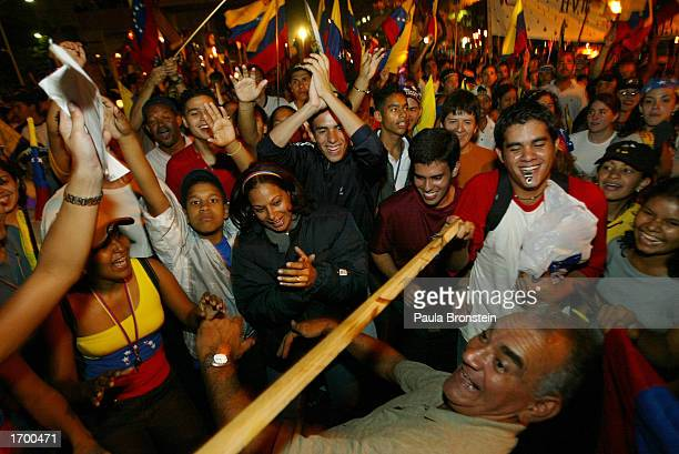 Venezuelan man does the limbo dance during a candlelight march and rally that drew nearly half a million protesters demanding early elections or...