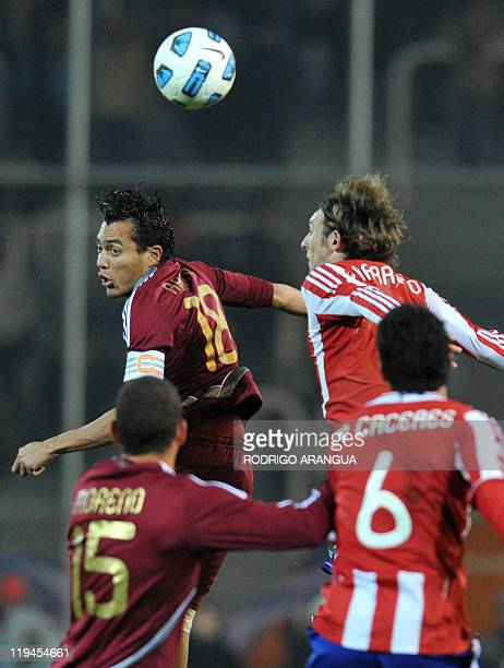 Venezuelan midfielder Juan Arango and Paraguayan midfielder Edgar Barreto jump for the ball during their 2011 Copa America semifinal football match...