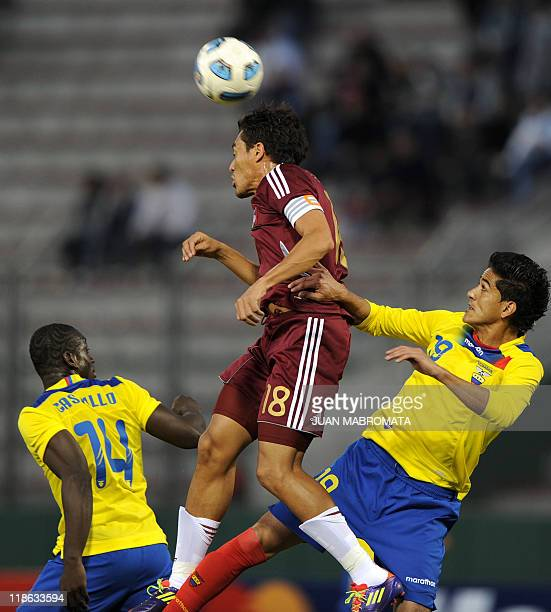 Venezuelan midfielder Juan Arango heads the ball under the mark of Ecuadorean midfielder Segundo Castillo and defender Norberto Araujo during a 2011...