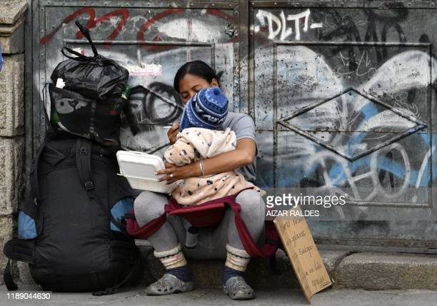 A Venezuelan migrant feeds her child as she begs in the streets of La Paz on December 10 2019 Thousands of Venezuelans fleeing economic and political...