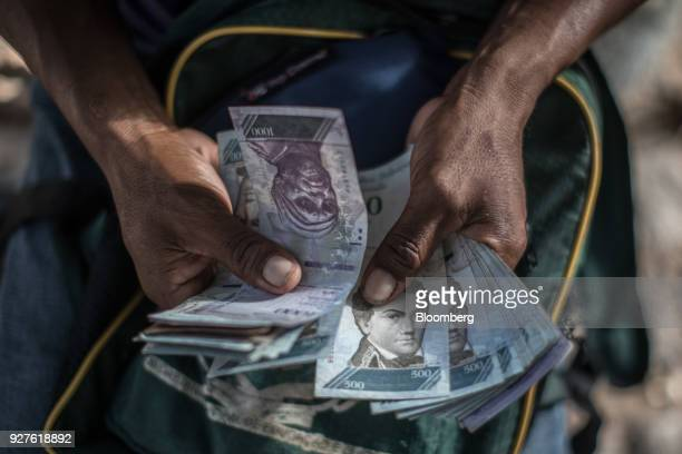 A Venezuelan migrant holds out Bolivar banknotes for a photograph at Simon Bolivar Square in Boa Vista Roraima state Brazil on Saturday Feb 17 2018...