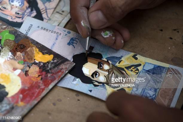 Venezuelan migrant Javier Ceballos paints a Venezuelan Bolivar bill with the image of late Colombian drug kingpin Pablo Escobar in a street in...