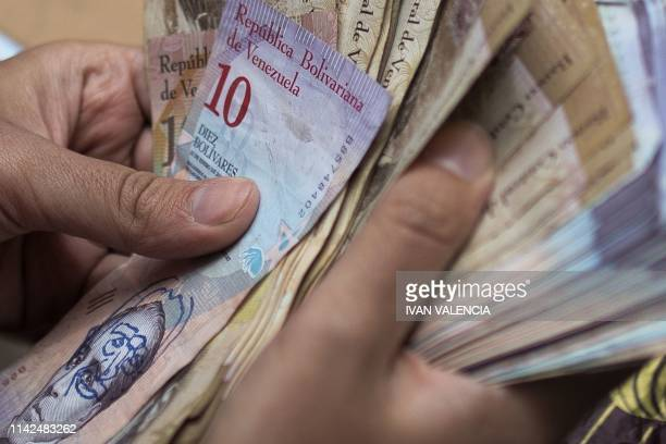 Venezuelan migrant Javier Ceballos, who paints Venezuelan Bolivar bills for a living, holds a roll of bills in a street in Bogota, Colombia, on May...