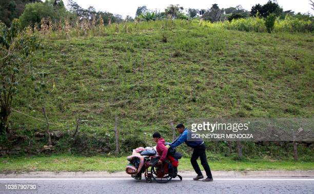 Venezuelan migrant Jefferson Alexis pushes his father Jose Agustin Lopez's wheelchair along the road linking Cucuta and Pamplona in Norte de...