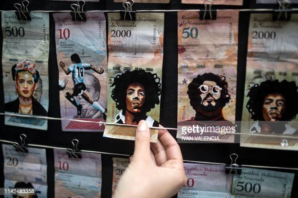 Venezuelan migrant Paula Villamizar shows Venezuelan Bolivar bills painted by her and her partner with iconic characters in a street in Bogota...