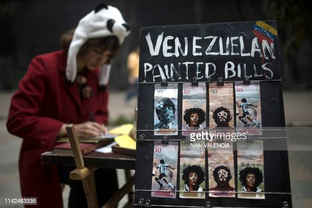TOPSHOT Venezuelan migrant Paula Villamizar who paints Venezuelan Bolivar bills for a living works in a street in Bogota Colombia on May 3 2019 A...