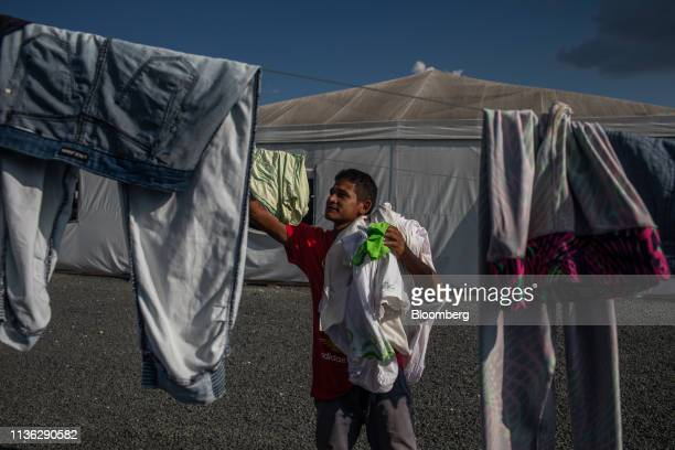 Venezuelan migrant removes clothing from a clothesline inside a refugee shelter near the Venezuelan border in Pacaraima, Brazil, on Wednesday, April...