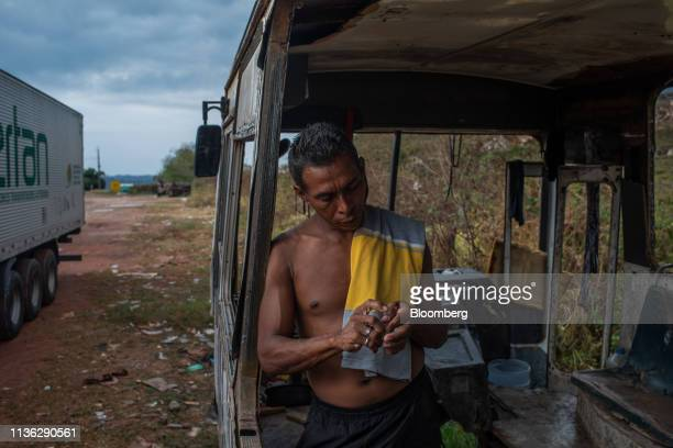 Venezuelan migrant stands in a makeshift shelter inside an abandoned bus near the Venezuelan border in Pacaraima, Brazil, on Wednesday, April 10,...