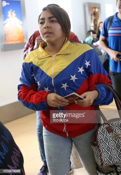 A Venezuelan migrant waits to enter the boarding area of the international airport in Lima after a group of Venezuelan nationals who chose to return...