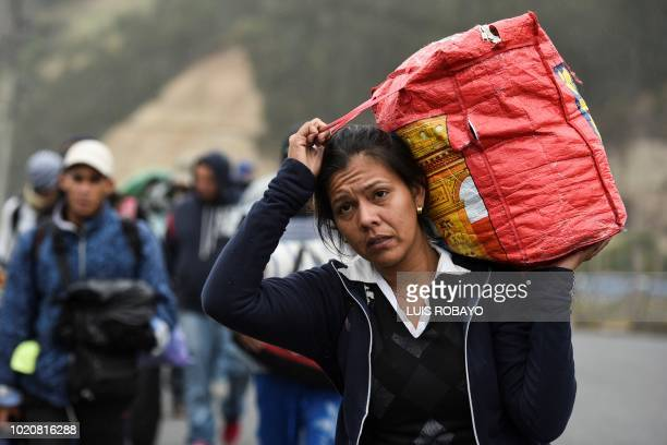 A Venezuelan migrant woman heading to Peru carries a bag as she walks along the Panamerican highway in Tulcan Ecuador after crossing from Colombia on...