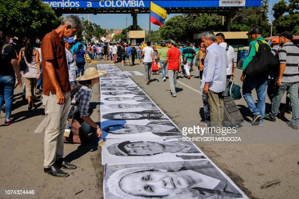Venezuelan migrants and others just crossing for the day into Colombia walk past portraits of Venezuelan migrants and refugees displayed on December...
