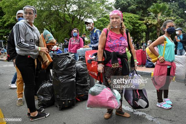 TOPSHOT Venezuelan migrants carry their luggage before boarding a bus to voluntarily return to their country because of the novel coronavirus COVID19...