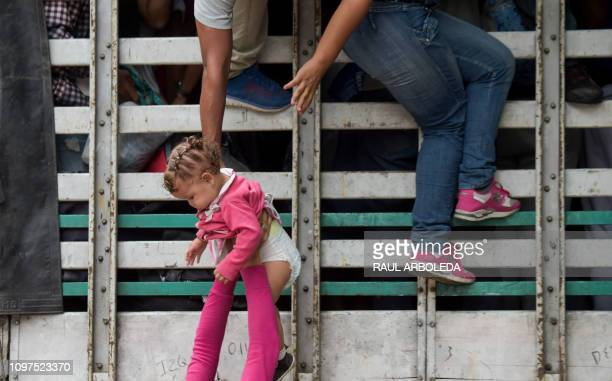 TOPSHOT Venezuelan migrants climb on a truck on the road from Cucuta to Pamplona in Norte de Santander Department Colombia on February 10 2019...