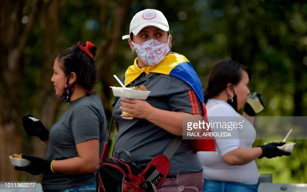 Venezuelan migrants have something to eat as they waiting to board a bus with the hope of being able to return to their country because of the novel...