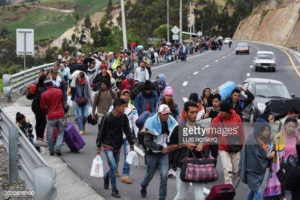 Venezuelan migrants heading to Peru walk along the Panamerican highway in Tulcan Ecuador after crossing from Colombia on August 21 2018 Ecuador...