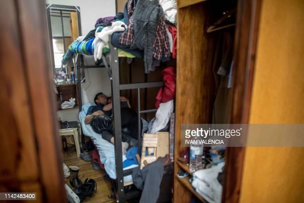 Venezuelan migrants Javier Ceballos and Paula Villamizar rest at their house in Bogota Colombia on May 3 2019 A couple of Venezuelan migrants paint...