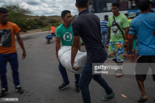 Venezuelan migrants move bags after arriving at a bus station near the Venezuelan border in Pacaraima, Brazil, on Wednesday, April 10, 2019....