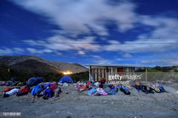 TOPSHOT Venezuelan migrants on their way to Peru sleep along the PanAmerican Highway between Tulcan and Ibarra in Ecuador after entering the country...