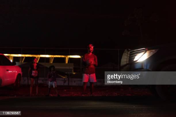 Venezuelan migrants stand at night near the Venezuelan border in Pacaraima, Brazil, on Wednesday, April 10, 2019. Venezuelan refugees looking for...