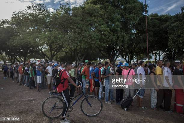 Venezuelan migrants wait in line to receive food donations at Simon Bolivar Square in Boa Vista Roraima state Brazil on Saturday Feb 17 2018 Hundreds...