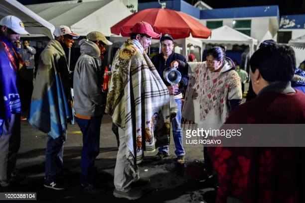 Venezuelan migrants waiting outside the Ecuadorean migration office at the Rumichaca international bridge in Tulcan Ecuador after crossing from...