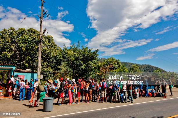 Venezuelan migrants wear a face masks as they queue to receive food and medicines from members of the Red Cross on a highway in Cucuta, Colombia, on...
