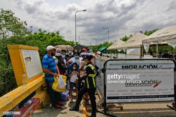 Venezuelan migration agent checks documents of people crossing the Francisco de Paula Santander International Bridge between Cucuta, Colombia, and...