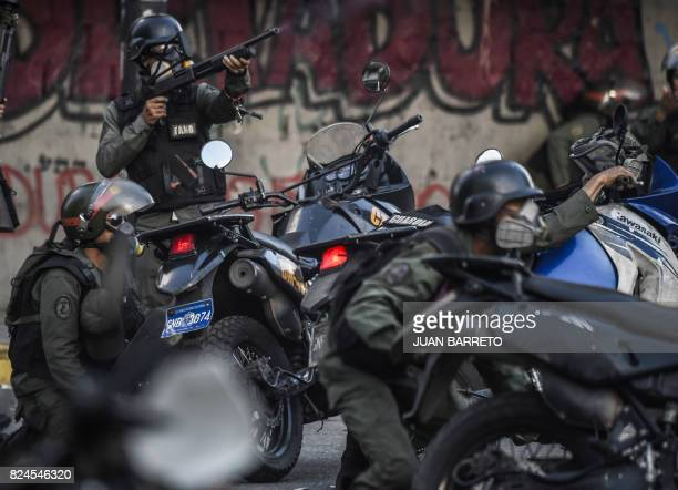 TOPSHOT Venezuelan National Guard motorcyclists take cover upon coming under fire during a confuse skirmish in Caracas on July 30 2017 Deadly...