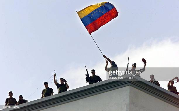 Venezuelan National Guard soldiers wave the national flag from the rooftop of the presidential palace Miraflores 13 April 2002 Hundreds of supporters...